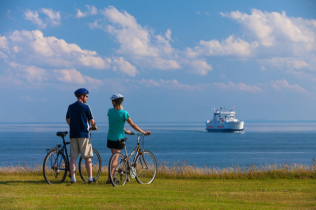 Two cyclists in field watching ferry crossing the water.