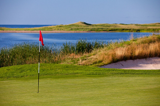 Red flag on golf green in front of bay with dunes behind water.