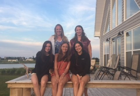 five young women sitting on a cottage deck