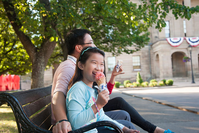 Girl eating ice cream cone sitting with man on a park bench.