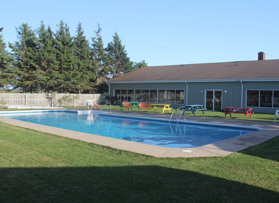 rectangular swimming pool with picnic tables neaby