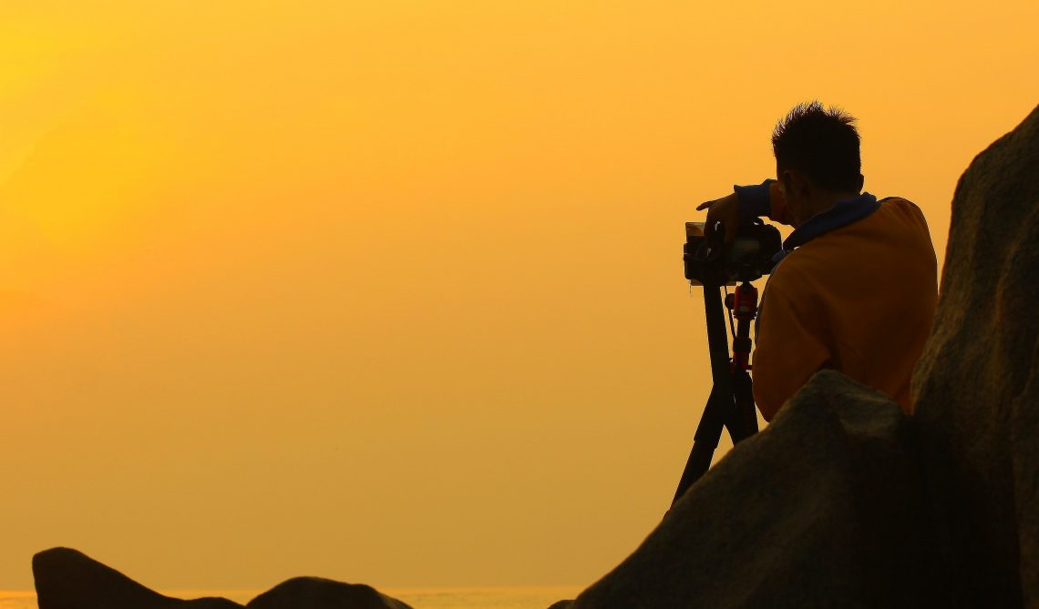Man taking photo at sunset