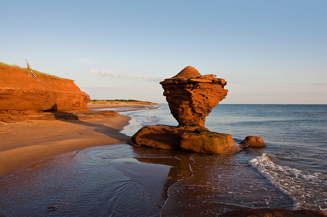 Tea Pot shaped rock formation on beach with waves washing on the sand