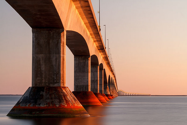 Support columns of the Confederation Bridge shaded in the rosy glow of sunset.