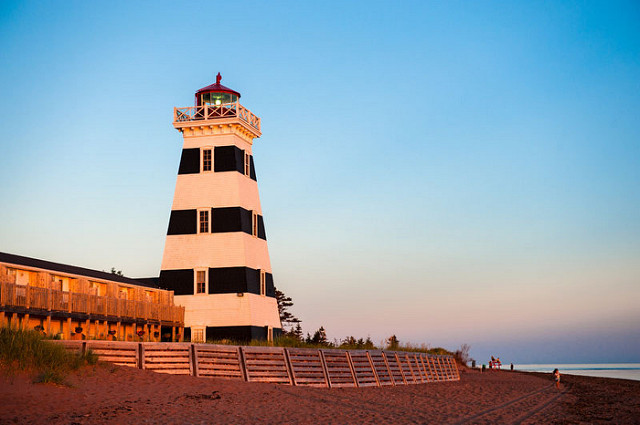 Square lighthouse with 4 horizontal black stripes with a red lantern on top.