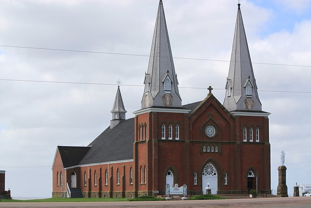 Red brick church with twin grey spires and white front door.