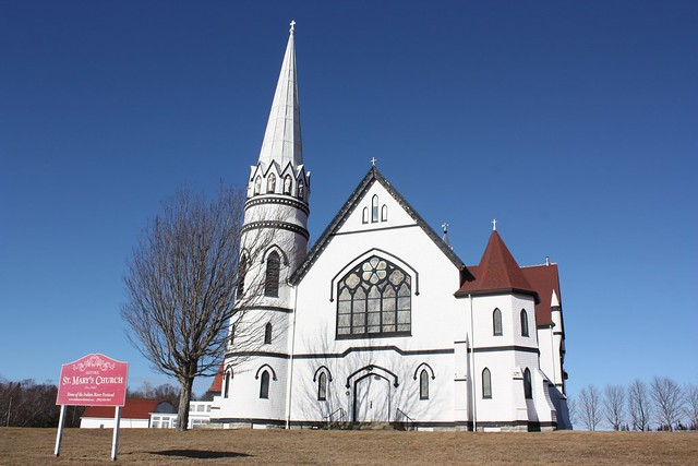 White church with red roof and one left hand spire. Very large stained glass window on front of church.