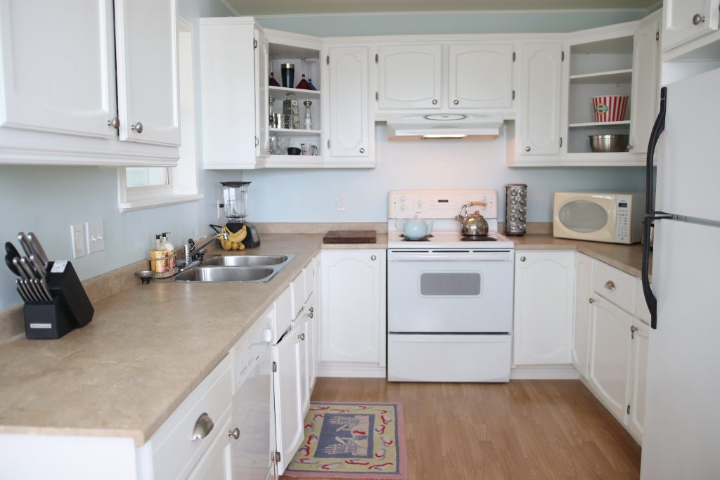 Kitchen with pale blue walls and white cupboards