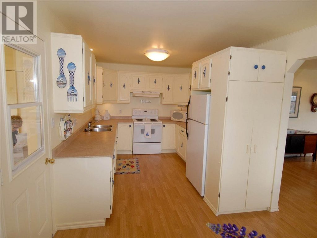 Kitchen with yellow cupboards, walls and ceiling.
