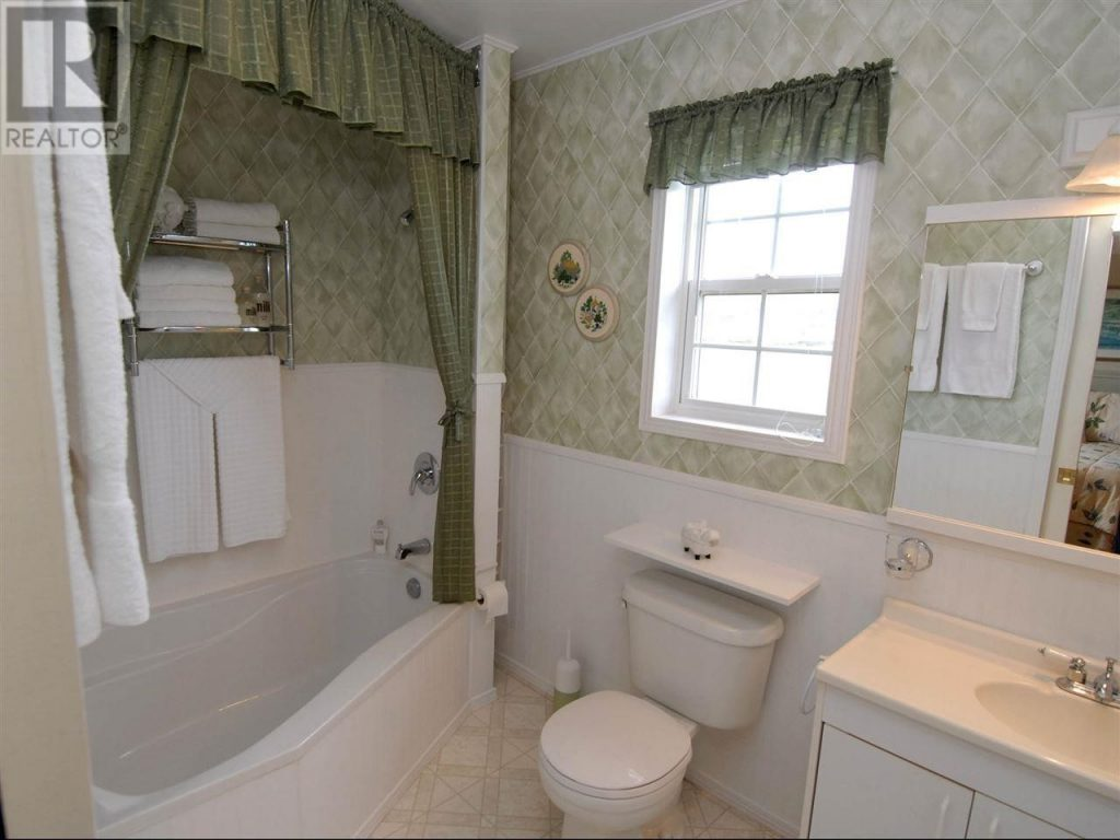 Green tiled bathroom with two person tub.